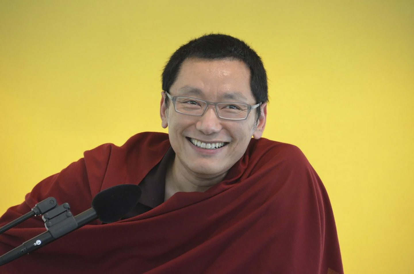 A smiling Buddhist monk with glasses